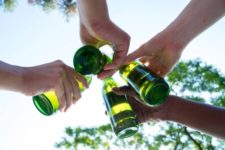 A group of friends toasting with beer in a garden