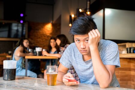 A sad handsome excluded asian boy sitting alone in a bar using his smartphone