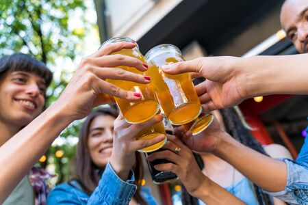 Closeup of a group of friends toasting with beer in a beergarden.