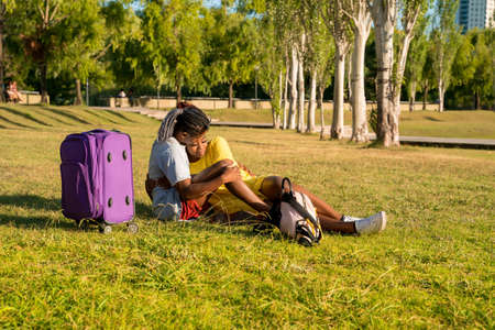 A happy young couple with luggage relaxing in a park while arriving to their destination.