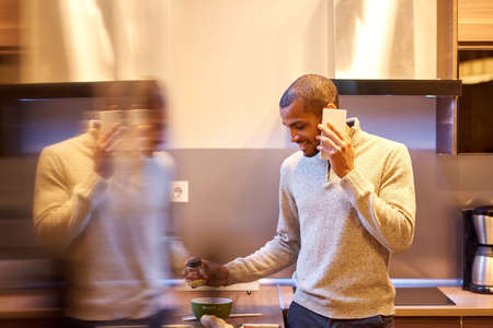A happy handsome young man talking on his phone and cooking in the kitchen. Banque d'images