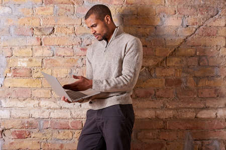A serious handsome young man using a laptop in a sweater. Banque d'images
