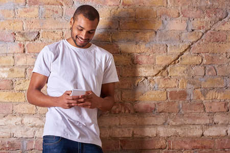 A happy handsome young man using his smartphone in a white tshirt and blue jeans. Banque d'images
