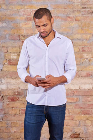 A serious handsome young man using his smartphone in a white shirt.