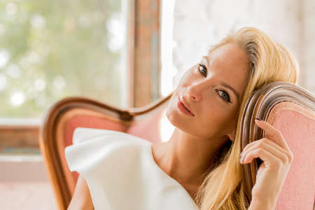 Portrait of a beautiful young woman sitting in a antique armchair.