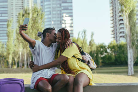 A travelling black couple taking selfies in a park during their summer trip.