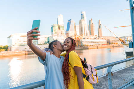 A happy loving couple taking a selfie in Puerto Madero in Buenos Aires. Banque d'images