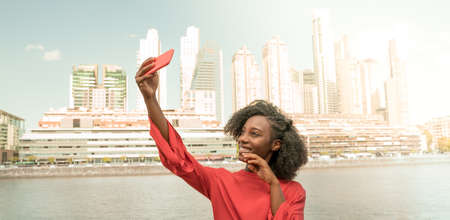 A cheerful young woman taking a selfie in Puerto Madero, Buenos Aires, Argentina.