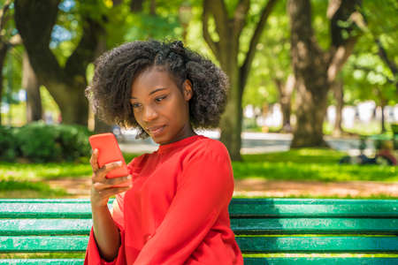 A beautiful black woman using her phone in a park.