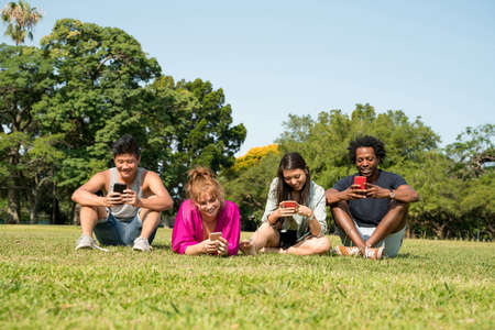 A multi-ethnic group of friends using their mobile phones while laying together in the park.