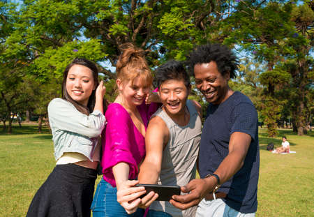 A group of friends having fun and taking selfies while enjoying a sunny day in a park.