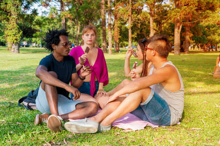 A group of friends enjoying ice cream together in a park on a sunny day. Banque d'images