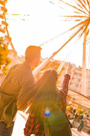 A traveling couple looking at a Ferris wheel on a sunny summer day.. Stock Photo