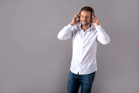 A smiling handsome young man in a white shirt listening to music on his headphones and standing in front of a grey background in the studio. Stock fotó