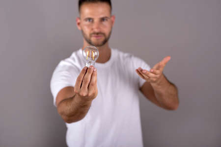 A serious young man in a white tshirt holding a lightbulb and standing in front of a grey background in the studio. Stock fotó