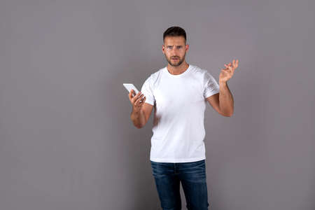 A surprised handsome young man in a white tshirt using his smartphone and standing in front of a grey background in the studio.