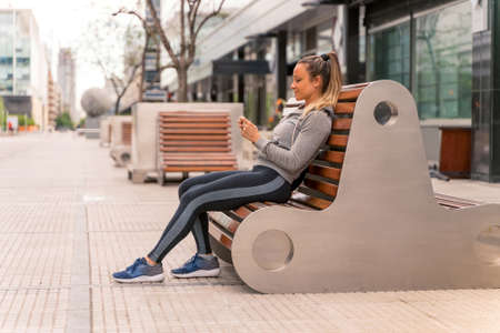 An athletic woman sitting on a bench and using her smartphone