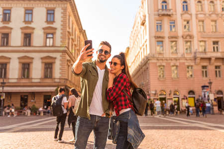 A happy couple taking a selfie in front of a historic landmark in a European city on a sunny summer day..