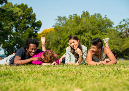 A group of friends laying together in the lawn in a park on a sunny summer day.