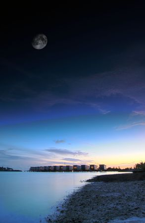 Water villas in the sunset at Kandooma island, Maldives