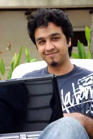 A young man using his laptop outdoors