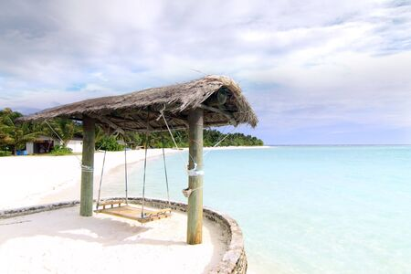 A rustic wooden swing by the beach at Rihiveli island, Maldives Stock Photo