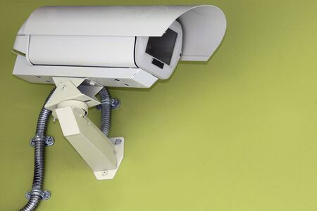 A security camera mounted on a green wall Stock Photo - 6104154