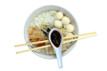 A bowl of Chinese flat noodles or koay teow with fish balls, fish cakes, bean sprouts and fuchuk