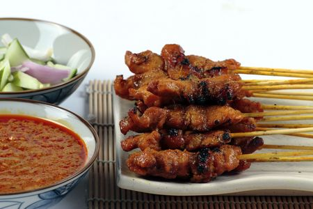 A plate of Chicken Satay served on a plate and bamboo mat with sliced onions, cucumber and a bowl of gravy Stock Photo
