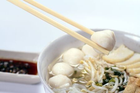 A pair of chopsticks holding a fish ball with a bowl of Chinese noodles and sauce in the background photo