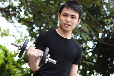muti: A young Asian man exercising with a dumb bell outdoors