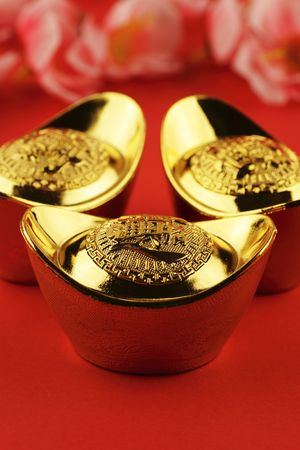 A trio of chinese gold ingots on a red background with some cherry blossoms in the background photo