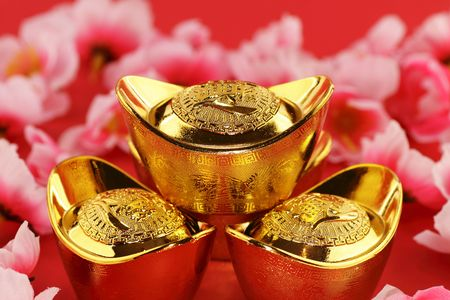 Front view of some chinese gold ingots surrounded by cherry blossoms on a red background Stock Photo - 6304603