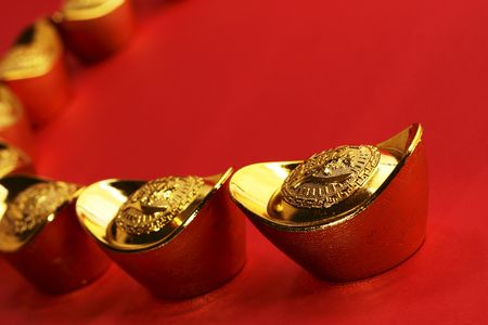 A curved row of traditional chinese gold ingots on a red background photo
