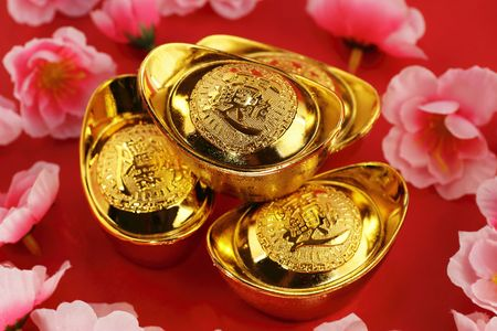 Top view of some chinese gold ingots surrounded by cherry blossoms on a red background Stock Photo - 6304602