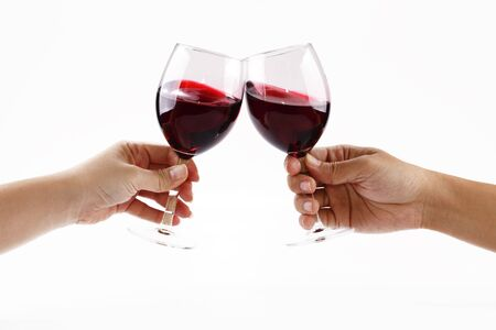 Two people toasting with wine glasses filled with red wine