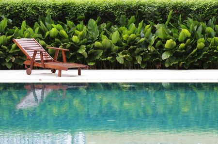 A wooden pool chair by the poolside Stock Photo