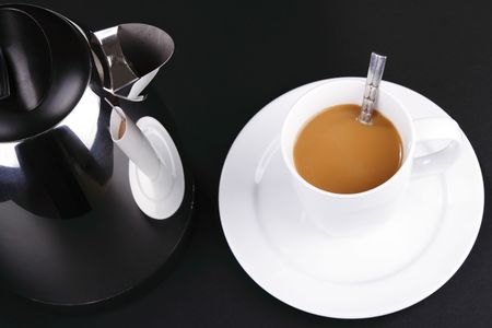 electric kettle: An electric kettle and a cup of coffee and saucer on a black background Stock Photo