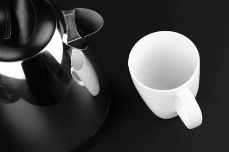 electric kettle: A stainless steel electric kettle and an empty coffee mug on a black background