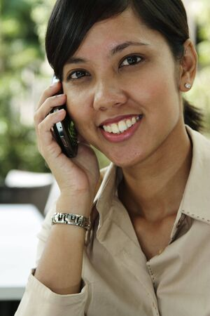A female young executive talking on the cellphone outdoors with greenery in the background