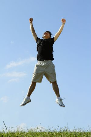 A college student jumping outdoors with a backpack Stock Photo