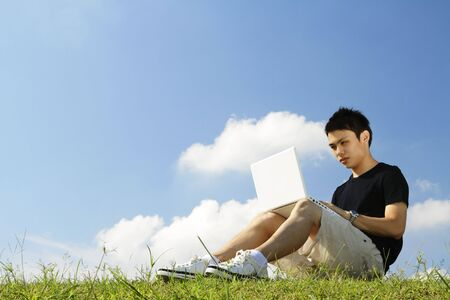 A young Asian college student working with a laptop outdoors Stock Photo