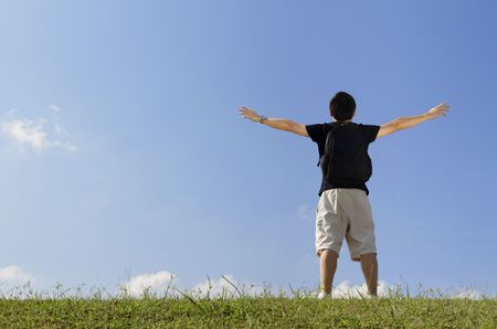 Rear view of a college student with his arms raised while standing outdoors photo