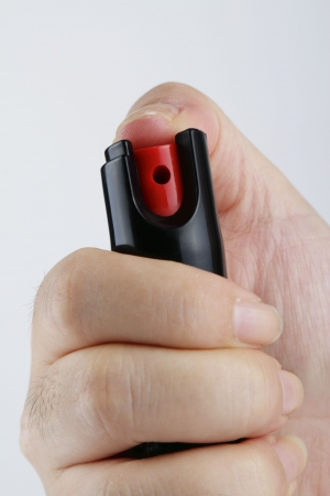 A womans hand holding a small bottle of pepper spray Stock Photo