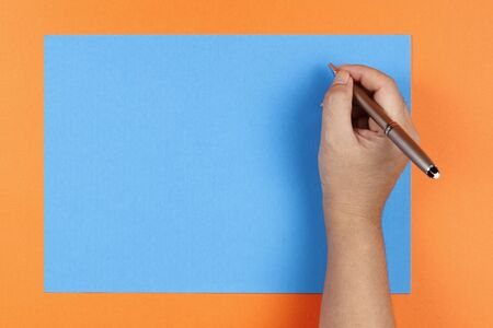 woman's hand: A womans hand holding a pen writing on colored blue paper on an orange background Stock Photo