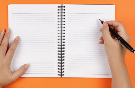 A pair of hands, a pen and a notebook on an orange background