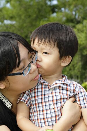 smooching: An Asian boy giving his mother a kiss