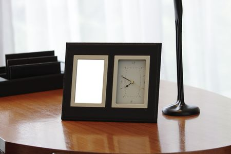 A modern photo frame and a clock on a wooden table Stock Photo