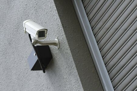 A security camera mounted on a wall outside a shop photo
