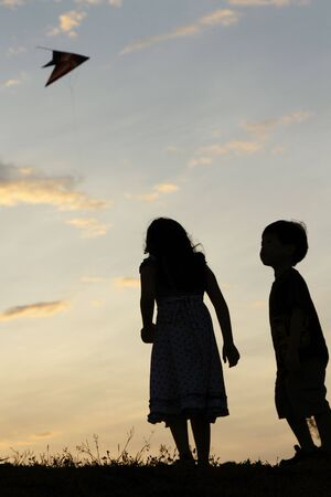 Two children watching a kite fly during sunset photo